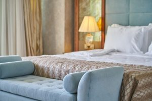 Wystrój pokoju hotelowego – jakie korzyści przyniesie nam szafa drewniana z lustrem?
